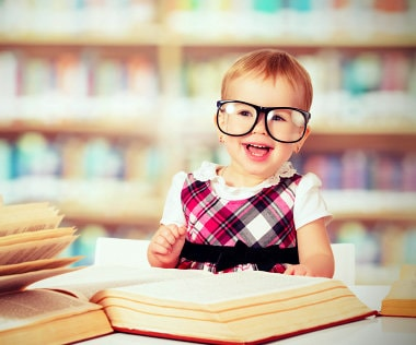 Cute little girl is reading some books